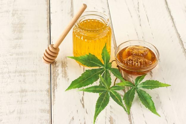 Cannabisblätter, marihuana und frischer organischer reiner honig im glasgefäß auf holztischhintergrund. honig-cbd-konzept.