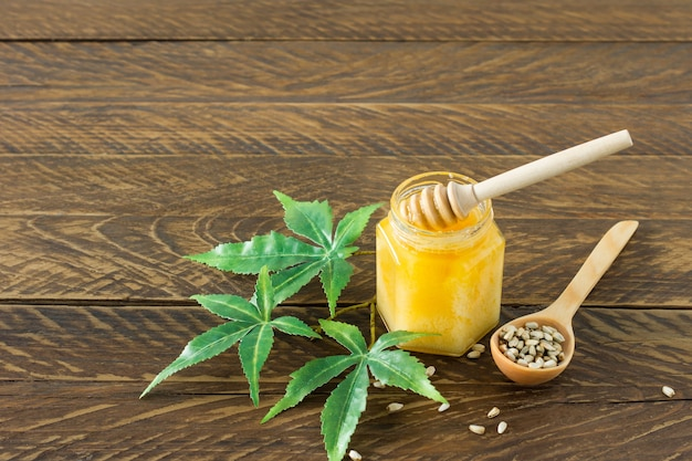 Cannabishonig in einer schüssel mit holz tiefer, hanfblätter und samen auf holztisch.