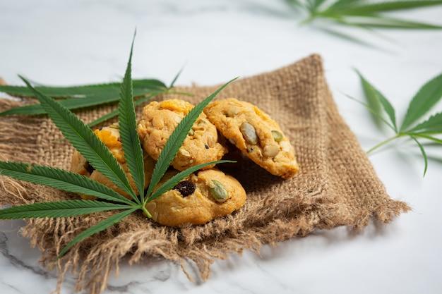 Cannabiskekse und cannabisblätter auf stoff gelegt