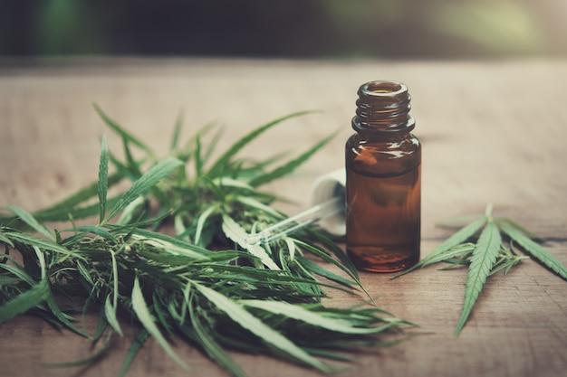 Cannabiskraut und blätter mit ölextrakten in gläsern. medizinisches konzept