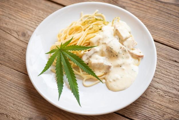 Cannabisnahrungsmittel-naturkräuterkonzept, spaghetti carbonara mit cannabisblatt - marihuanablätter