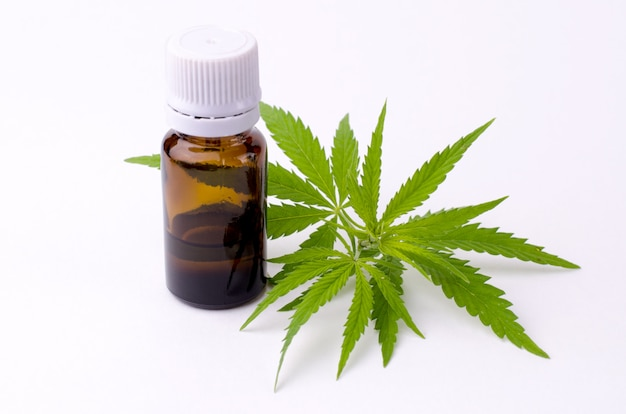 Cannabispflanzenblätter und cannabisextraktöl in der flasche.
