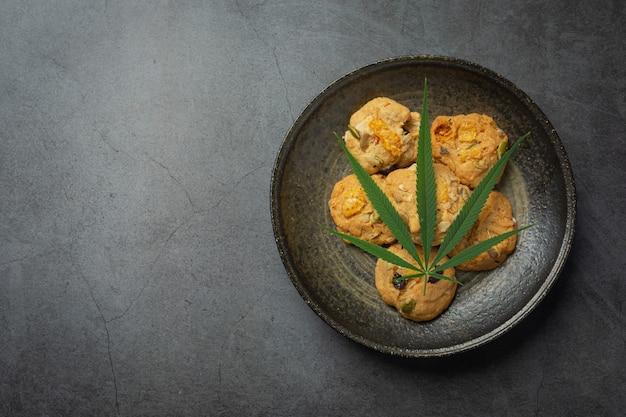 Cannabisplätzchen und cannabisblatt auf schwarzen teller gelegt