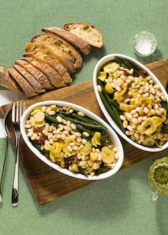 Cannellini nahrhafter weißer bohnensalat mit grünen bohnen, sonnengetrockneten tomaten und artischocken in öl. traditionelles italienisches essen