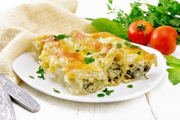 Cannelloni gefüllt mit hüttenkäse und spinat mit bechamelsauce in einem teller, handtuch, tomaten und petersilie auf holzbretthintergrund