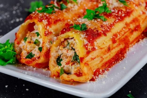 Cannelloni-teigwarenfleisch und bechamelsoße und nahaufnahme des basilikums auf dem tisch