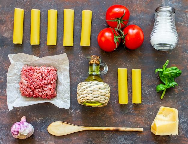 Cannelloni, tomaten, hackfleisch und andere zutaten. dunkler hintergrund. italienische küche.