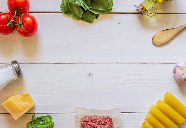 Cannelloni, tomaten, hackfleisch und andere zutaten. weißer hölzerner hintergrund. italienische küche.