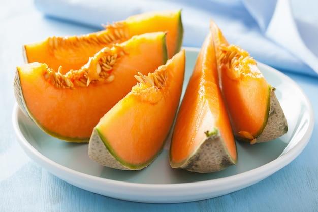 Cantaloupe melone auf blauem teller geschnitten