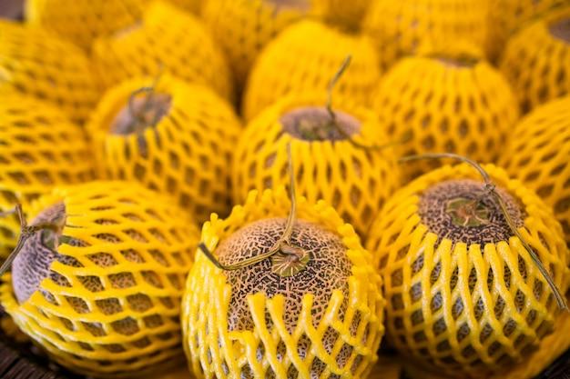 Cantaloupe melone in marktverpackung von schaumstoff über obst verkauft.