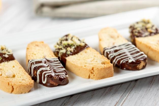 Cantuccini-kekse. italienisches biscottiplätzchen auf weißer platte auf einem weißen hölzernen hintergrund. ansicht von oben