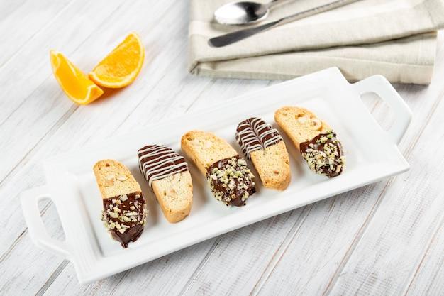 Cantuccini-kekse. italienisches biscottiplätzchen auf weißer platte auf einem weißen hölzernen hintergrund.