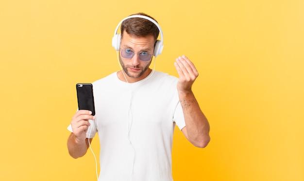 Capice oder geldgeste machen, sie auffordern, zu bezahlen, musik mit kopfhörern und einem smartphone hören