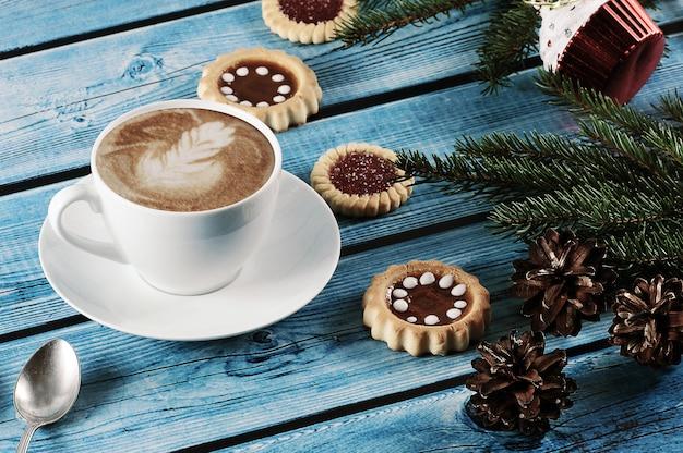 Cappuccino auf dem weihnachtshintergrund mit tannenbaum, kegel, plätzchen