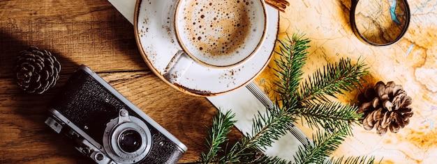 Cappuccino auf einem holztisch, touristenkarte und kamera. langes banner