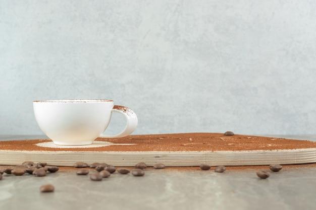 Cappuccino auf holzbrett mit kaffeebohnen.