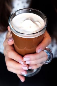 Cappuccino durch das glas, das von einer frau gehalten wird.