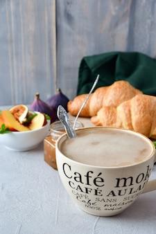 Cappuccino-frühstück mit croissant, frischer apfelmarmelade und obstsalat. frühstücksmenü