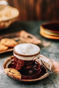 Cappuccino in der kaffeetasse auf dunklem rustikalem hintergrund