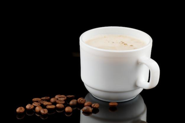 Cappuccino in einer tasse und kaffeebohnen