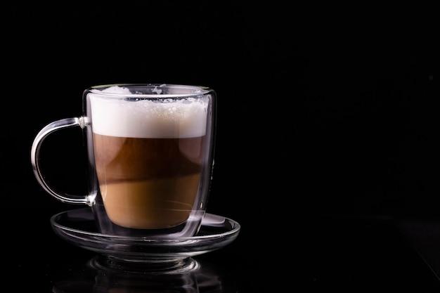 Cappuccino-kaffee in einer transparenten tasse auf einem schwarzen hintergrund.