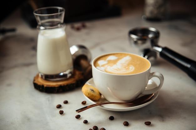 Cappuccino-kaffee zum frühstück mit milch und keksen auf einem weißen marmortisch