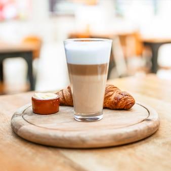 Cappuccino-Kaffeeglas mit Hörnchen auf hölzernem Behälter