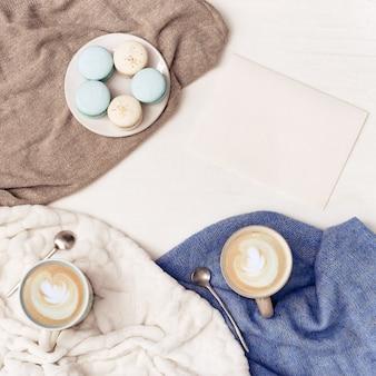 Cappuccino-kaffeekunst im großen becher und in den süßen makronen auf haupttisch mit warmer gestrickter kleidung. gemütliche umgebung zum trinken von morgendlichen heißgetränken. flach liegen.