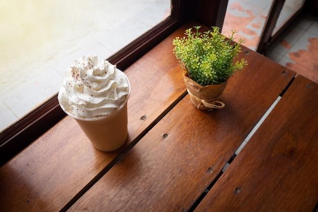 Cappuccino mischung in plastikbecher. serviert auf holztisch im café.