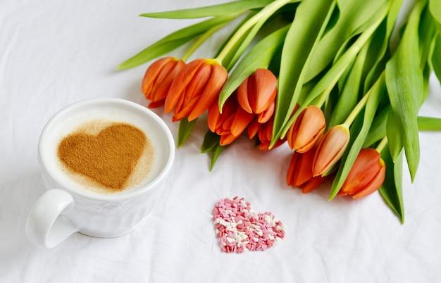 Cappuccino mit herzen von zimt-und blumen-zusammensetzungs-tulpen, valentinsgruß-tagesfrühlings-konzept