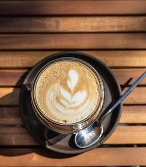 Cappuccino mit latte art im café im freien oder im kaffeehaus selektiver fokus sonniger morgen