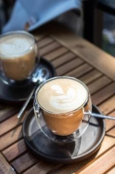 Cappuccino mit latte art in der tasse im café im freien oder im kaffeehaus selektiver fokus sonniger morgen