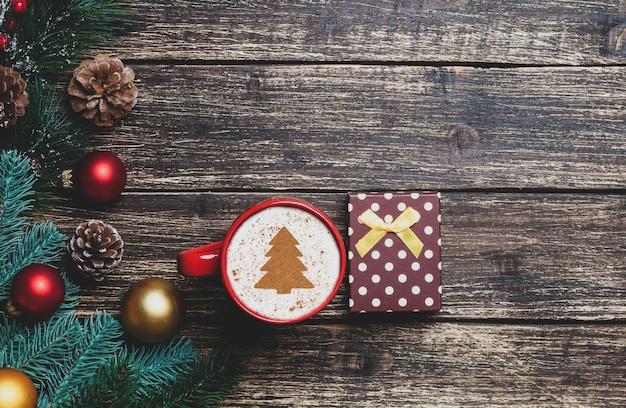 Cappuccino mit weihnachtsbaumform und -geschenk auf holztisch.