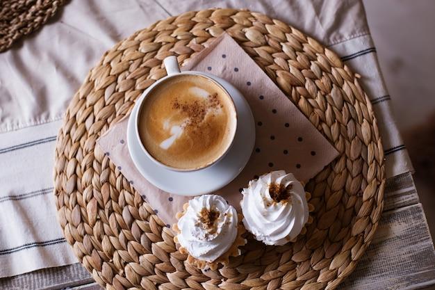 Cappuccino mit zimt, kuchen mit luftiger weißer sahne auf einer strohserviette, draufsicht
