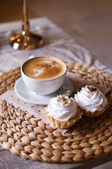 Cappuccino mit zimt, kuchen mit luftiger weißer sahne auf einer strohserviette