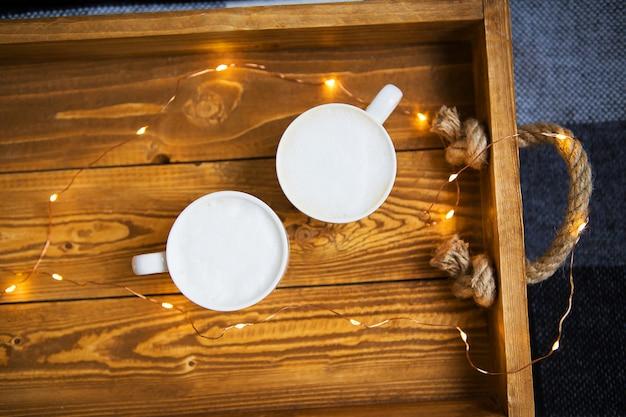 Cappuccino mit zwei schalen stehen auf einem hölzernen behälter mit lichtern