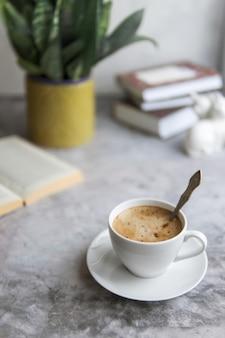 Cappuccino oder kaffeetasse und buch auf beton grau tisch