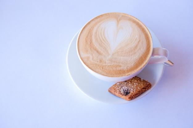 Cappuccino oder latte kaffee in einer tasse mit milchschaum und keksen. tasse kaffee mit mandelbiscotti. latte mit herz design.