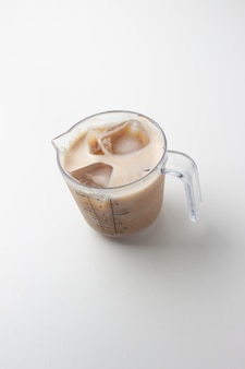Cappuccino oder latte mit schaumigem schaum in einem messbecher auf weißem hintergrund