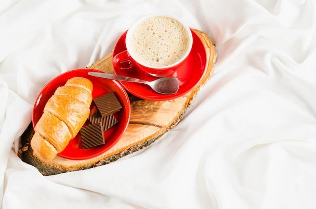 Cappuccino, schokolade und hörnchen auf einem bett.