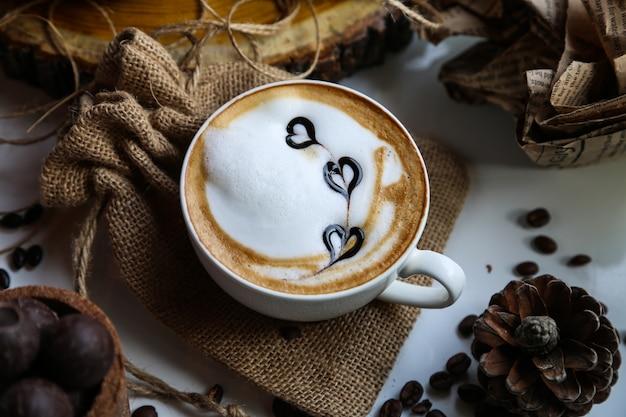 Cappuccino-tasse von der seitenansicht auf sack mit tannenzapfen