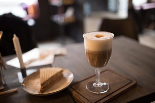 Cappuccino und ein stück kuchen auf einem tisch in einem café.
