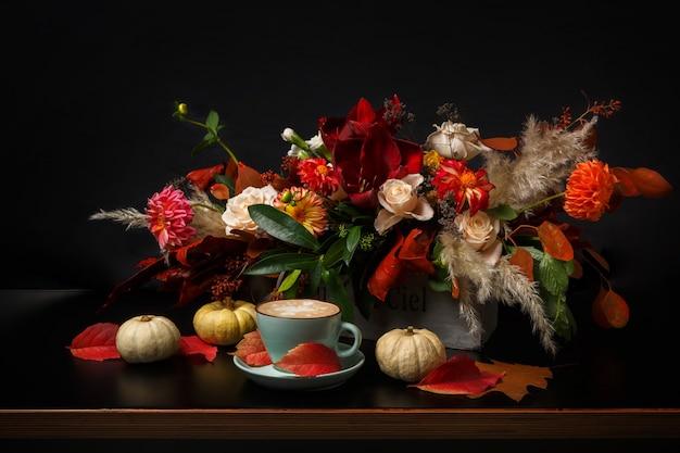 Cappuccino und schöne blumen stillleben. blumenladen zusammensetzung. kaffeetasse mit schaum, apfel, frischem und getrocknetem blumenstrauß auf schwarzem holztisch. floristische kunst und blumenmusterkonzept