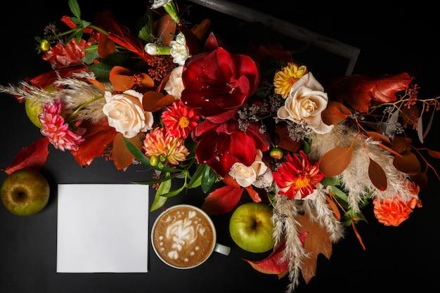 Cappuccino und schöne blumen stillleben. zusammensetzung der draufsicht des blumenladens. kaffeetasse, apfel, frisch und blumenstrauß auf schwarzem holztisch. floristische kunst und blumenmusterkonzept