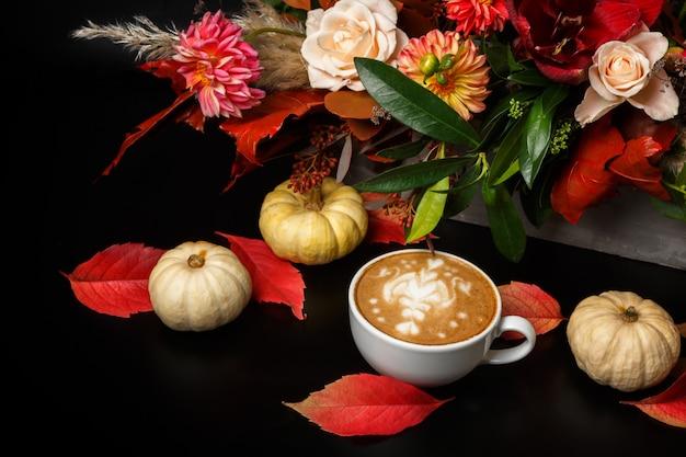 Cappuccino und schöne blumenstrauß stillleben. blumenladen zusammensetzung. kaffeetasse, kürbisse auf schwarzem holztisch. floristische kunst und blumenmusterkonzept