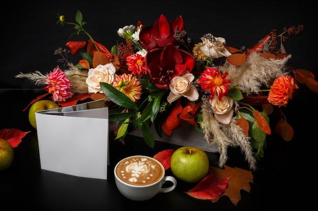 Cappuccino und schöne blumenzusammensetzung. blumenladen zusammensetzung. kaffeetasse mit schaum, apfel, frischem und getrocknetem blumenstrauß auf schwarzem holztisch. floristische kunst und blumenmusterkonzept
