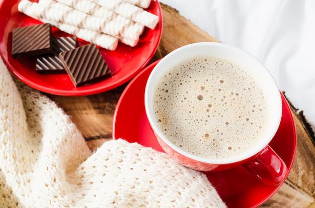Cappuccino und schokolade auf einem bett mit plaid.