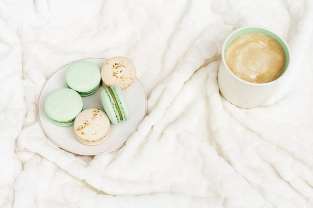 Cappuccino und süßigkeiten zum frühstück. tasse kaffee und makronen