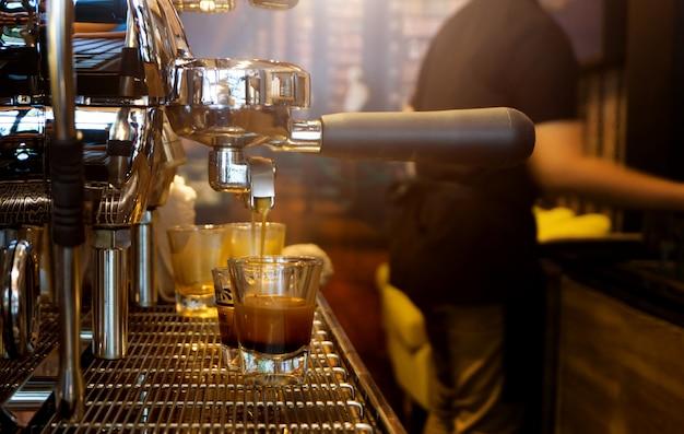 Cappuccinokaffee, der aus kaffeemaschine gießt, nahaufnahmen