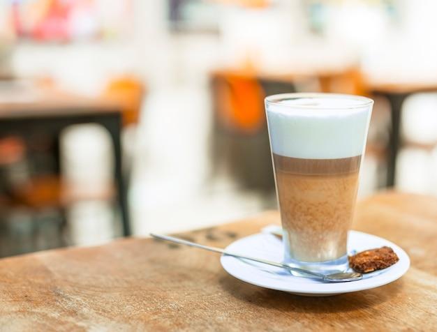 Cappuccinokaffee in einem transparenten glas auf tabelle